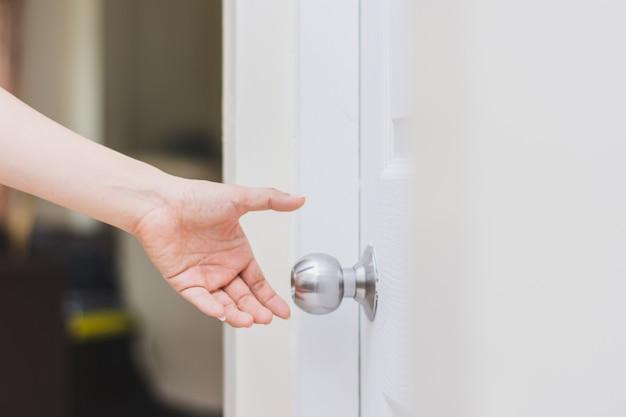 Gros plan de la main de la femme atteignant le bouton de la porte, ouvrant la porte