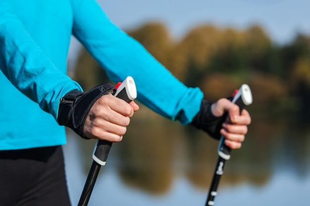 Gros plan de la main de femme avec des bâtons de marche nordique