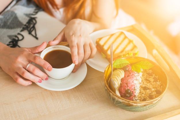 Gros plan, main femme, bol, flocons avoine, fruit, plateau
