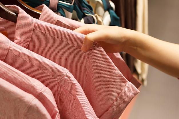 Gros plan de la main de femme choisissant un t-shirt.