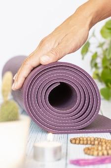 Gros plan de la main d'une femme dépliant un tapis de yoga violet, de mauvaises perles de bois sur du bois blanc. accessoires indispensables pour pratiquer le yoga et la méditation.