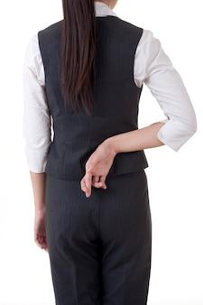 Gros plan d'une main de femme avec les doigts croisés derrière le dos.