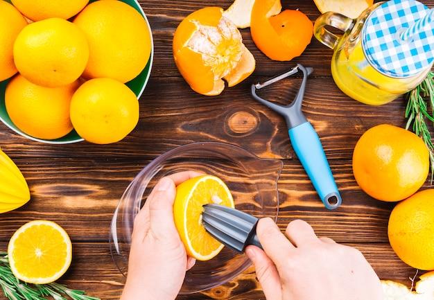Gros plan, de, main femme, faire, jus orange frais, sur, table en bois