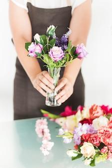 Gros plan, main femme, fleurs, vase