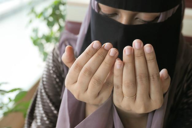 Gros plan de la main de femme musulmane priant au ramadan
