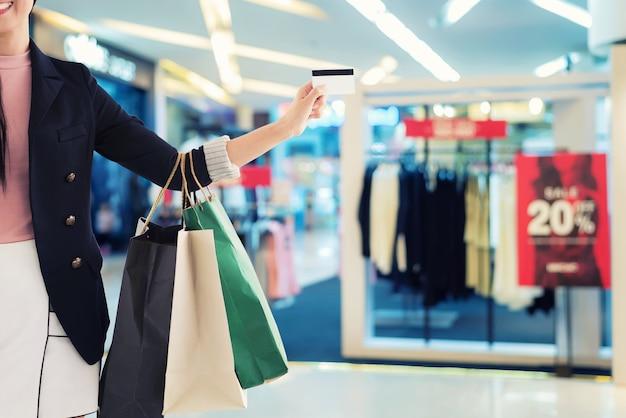 Gros plan d'une main de femme avec de nombreux sacs à provisions et carte de crédit sur le fond du centre commercial.