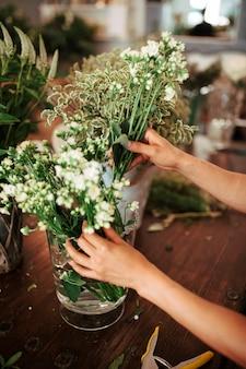Gros plan d'une main de femme organisant des fleurs dans un vase