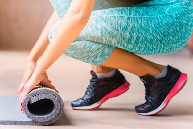Gros plan, main femme, plier, tapis exercice