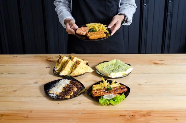 Gros plan de la main de la femme présentant sa savoureuse nourriture sur l'assiette photo gratuit