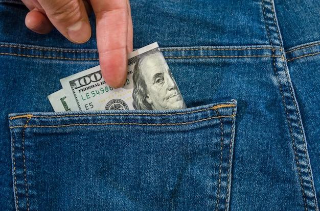 Gros plan d'une main de femme sort un billet de cent dollars d'une poche de jeans