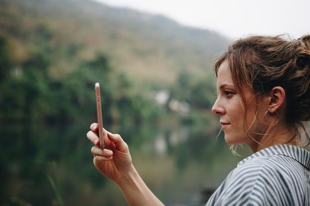 Gros plan d'une main de femme soulevant son smartphone en prenant une photo de la nature