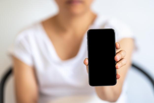 Gros plan de la main de femme tenant et montrer le smartphone mobile écran noir isolé blanc.