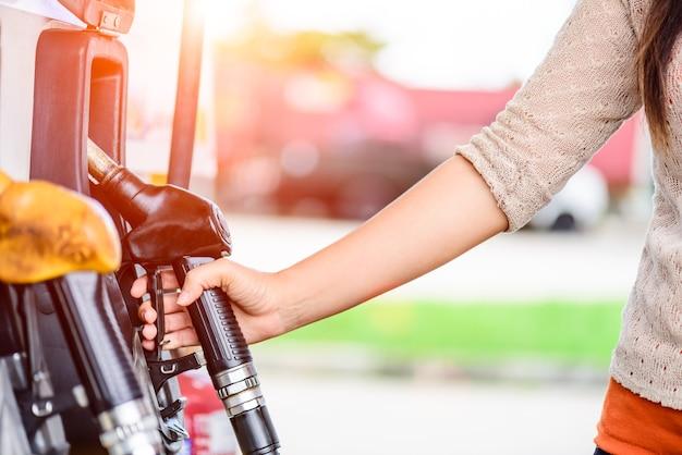 Gros plan d'une main de femme tenant une pompe à essence à une station