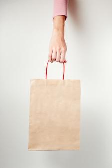 Gros plan d'une main de femme tenant un sac en papier