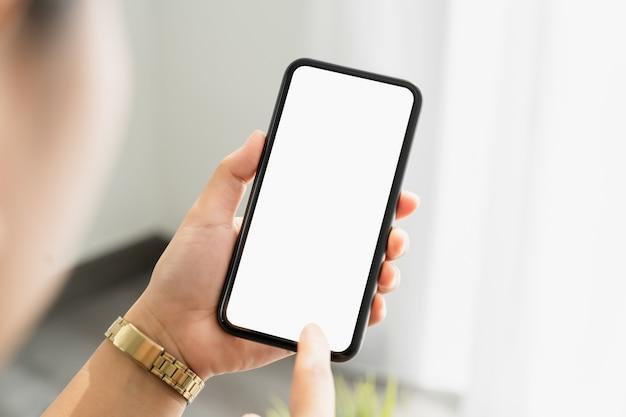 Gros plan de la main de femme tenant le smartphone et l'écran est vide, concept de réseau social.