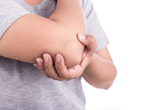 Gros plan la main de la femme tenant son coude isolé sur fond blanc. concept de douleur de coude.