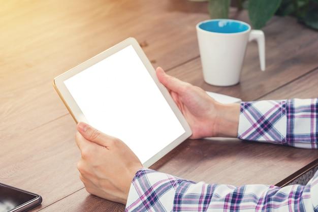Gros plan main femme tenant la tablette écran vide sur la table en bois avec la lumière du soleil