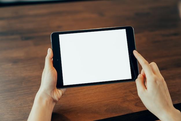 Gros plan d'une main de femme tenant une tablette numérique sur la table et l'écran est vide.