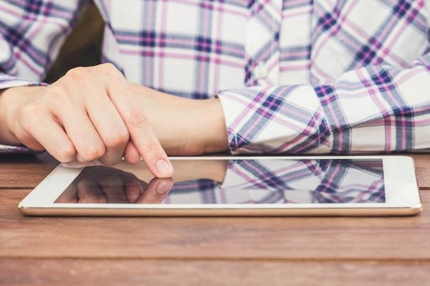 Gros plan main femme tenant la tablette sur la table en bois avec la lumière du soleil.