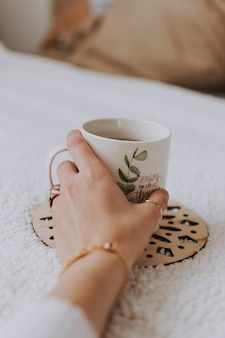 Gros plan d'une main de femme tenant une tasse blanche avec une peinture posée sur une surface blanche