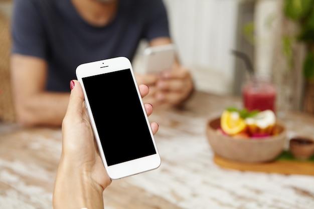 Gros plan de la main de la femme tenant un téléphone mobile générique avec écran blanc
