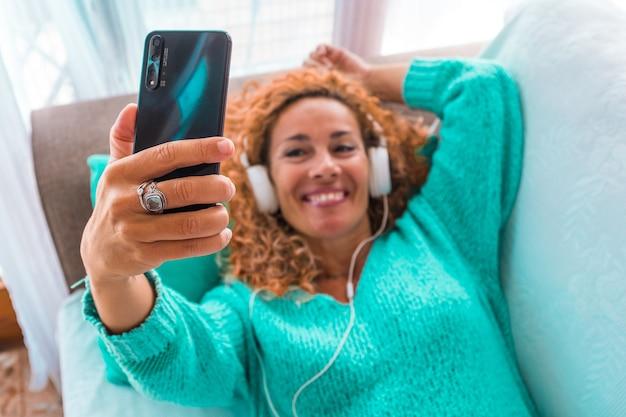 Gros plan sur la main d'une femme tenant un téléphone et prenant un selfie de sa musique écoutant avec des écouteurs et souriant à la maison sur le canapé
