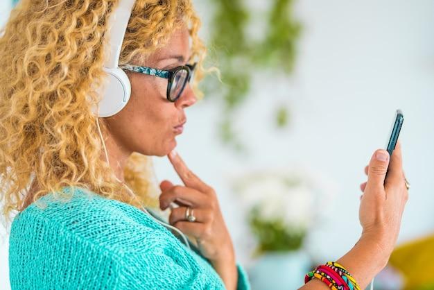 Gros plan sur la main d'une femme tenant un téléphone et prenant un selfie de sa musique écoutant avec des écouteurs et souriant à la maison