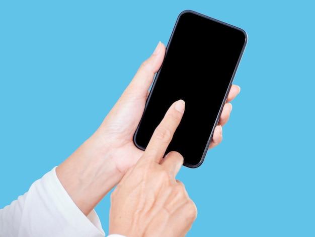 Gros plan de la main de la femme touchant un écran blanc smartphone sur fond bleu