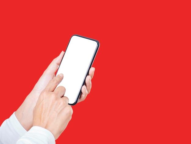 Gros plan de la main de la femme touchant un écran blanc smartphone isolé sur fond rouge