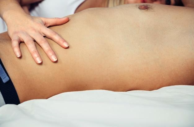 Gros plan sur une main de femme touchant le torse d'un homme torse nu dans la journée