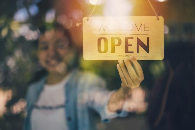 Gros plan d'une main de femme tournant un panneau d'affichage ouvert sur une porte vitrée dans un café et un restaurant.