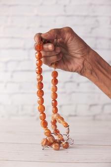 Gros plan de la main de femmes âgées priant au ramadan.
