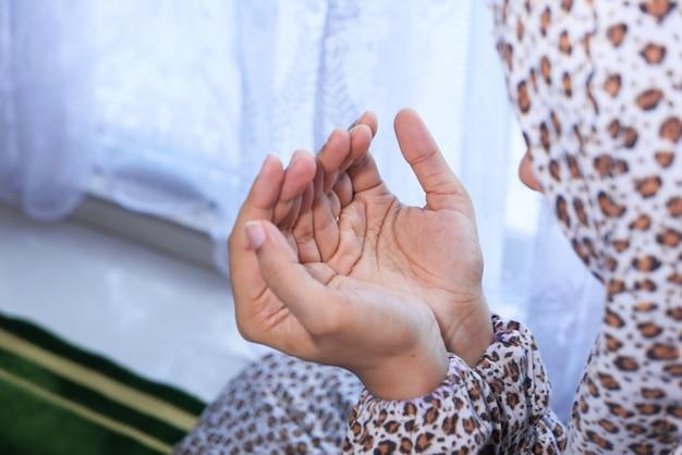Gros plan de la main de femmes musulmanes priant.