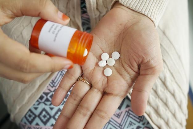 Gros plan de la main des femmes prenant des pilules