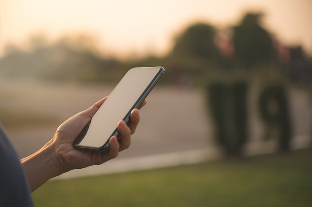 Gros plan de la main des femmes tenant et utiliser le smartphone pour les réseaux sociaux, la messagerie ou les achats en ligne. gens heureux avec le concept d'entreprise technologique.