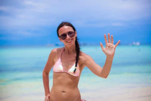 Gros plan d'une main de fille avec coeur sur la paume peinte par la crème solaire