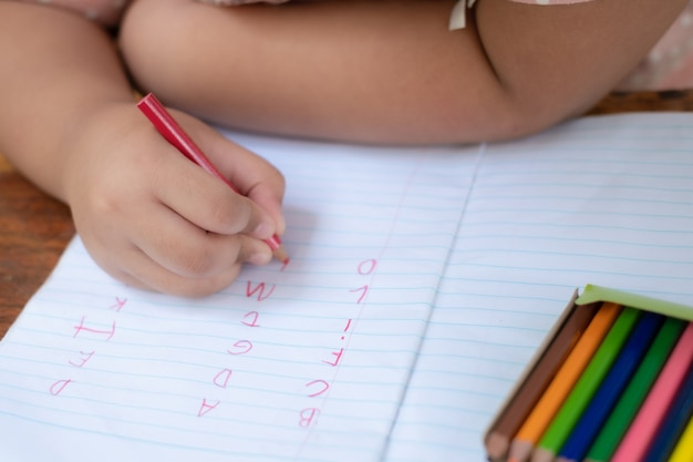 Gros plan de la main de la fille avec un crayon écrit des mots anglais à la main sur du papier bloc-notes blanc
