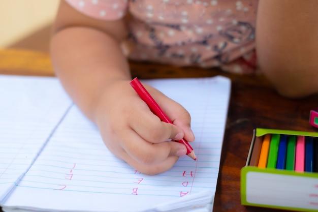 Gros plan de la main des filles avec un crayon écrit des mots anglais à la main sur du papier bloc-notes blanc