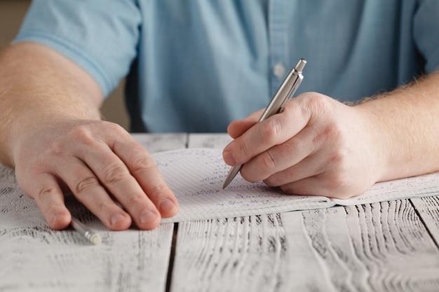 Gros plan de la main gauche de l'homme écrit sur papier, écrit des mathématiques en désordre, étudiant tenant un stylo à faire ses devoirs à la maison, calcule les résultats sur papier, concept d'éducation