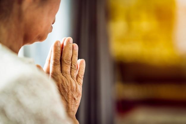 Gros plan la main de grand-mère prie pour le respect de la foi, de la spiritualité et de la religion