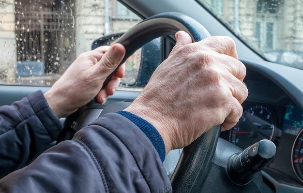Gros plan sur la main d'un homme adulte dans une voiture de tourisme, tenant le volant par temps froid et pluvieux dans la ville. l'homme conduit la voiture.