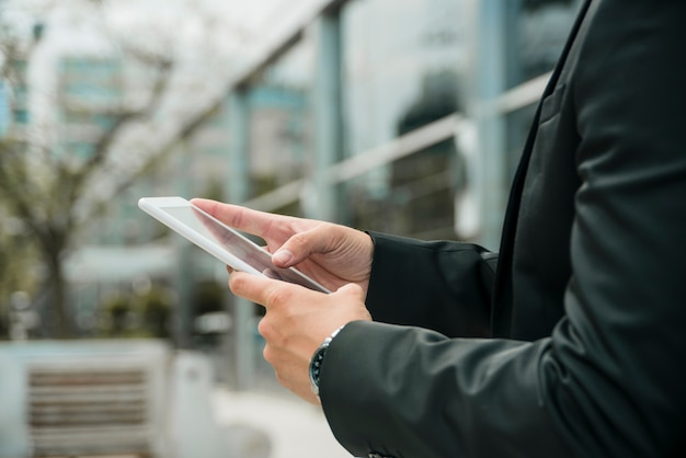 Gros plan de la main de l'homme d'affaires à l'aide du téléphone mobile à l'extérieur