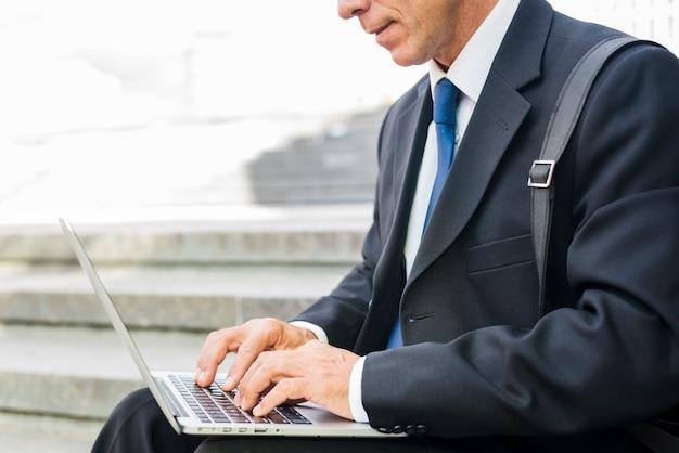 Gros plan de la main d'un homme d'affaires à l'aide d'un ordinateur portable