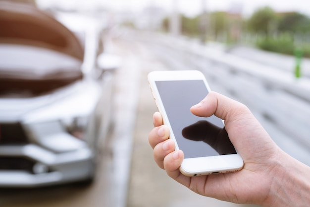 Gros plan de la main d'homme d'affaires à l'aide d'un téléphone intelligent mobile appeler un mécanicien automobile demander de l'aide parce que la voiture est cassée en bordure de route.