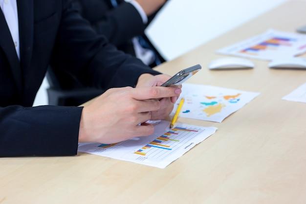 Gros plan sur la main de l'homme d'affaires à l'aide de téléphone mobile sur le bureau.