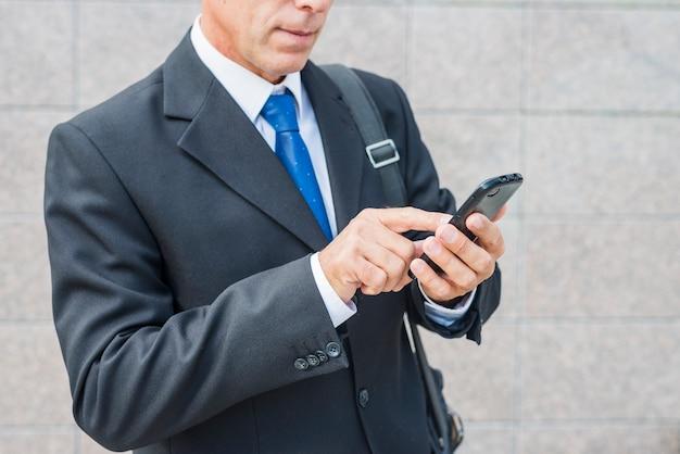 Gros plan de la main d'un homme d'affaires à l'aide d'un téléphone portable