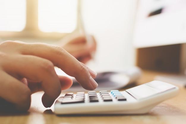 Gros plan main de l'homme d'affaires comptable comptable et à l'aide de la calculatrice avec ordinateur