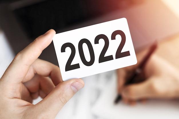 Gros plan sur la main l'homme d'affaires garde la carte avec le texte 2022. document, stylo et ordinateur portable.
