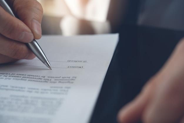 Gros plan de la main d'homme d'affaires avec un stylo signant un contrat commercial sur la table de bureau