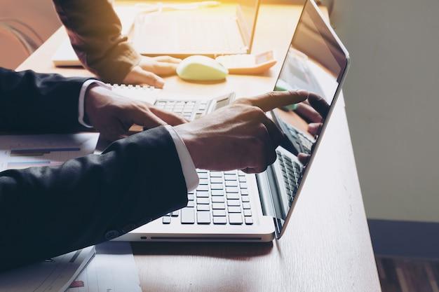 Gros plan de la main de l'homme d'affaires supervise le travail de son assistant sur l'ordinateur portable